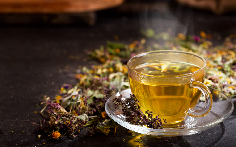 a glass cup of herbal tea with various herbs scattered around and behind the cup