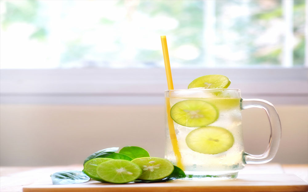 a tall glass pitcher of water with lemon slices in it and sliced limes next to the pitcher