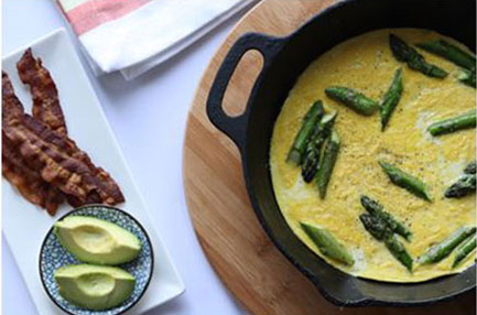 asparagus and bacon frittata in a cast iron pan on the right three slices cooked bacon two avocado slices on the left