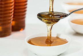 honey pouring down into a spoon