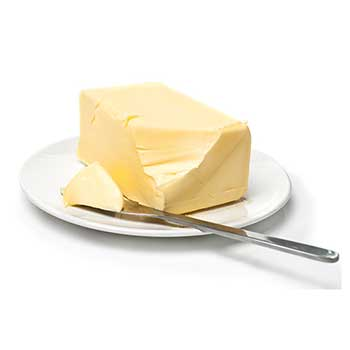 a block of butter with one corner cut off by the knife resting on the plate