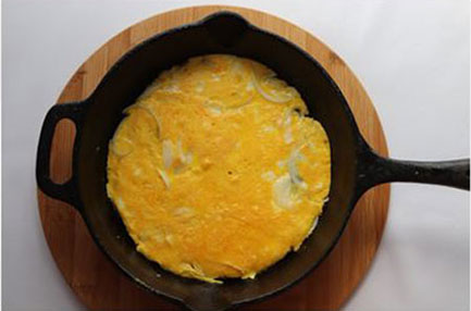 a cooked cheese and onion omelet in a cast iron frying pan