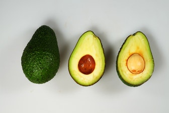 one whole avocado on the left two halves of a cut open avocado on the right