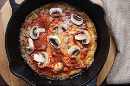 skillet pizza with sauce and mushrooms on top in a cast iron skillet