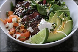 keto steak salad with slices of lime and avocado in a white bowl