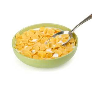 a bowl of flaked cereal with milk and a spoon resting in it